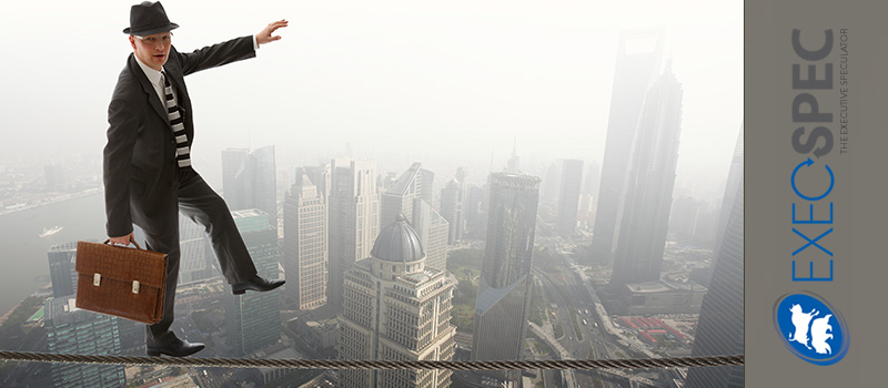 business man in suit performing a tightrope act over the Shanghai skyline